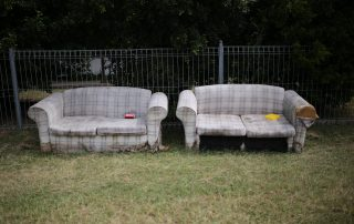two old sofas in a field